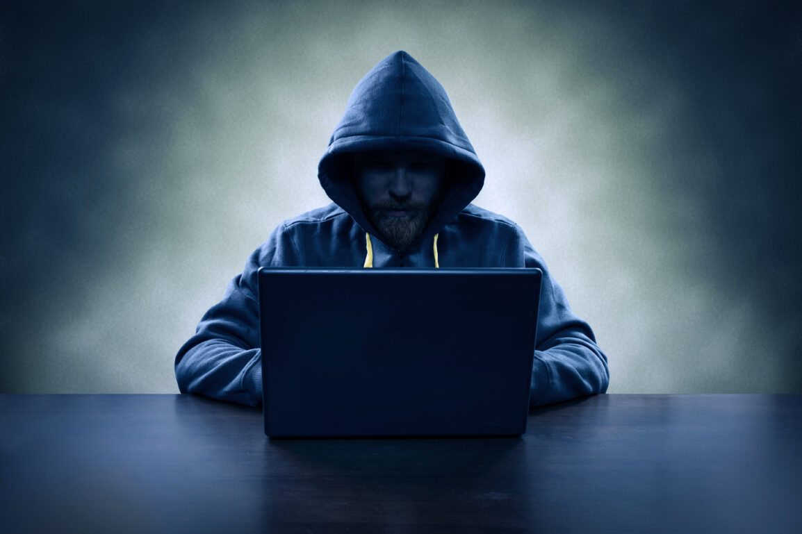 Identifying Computer hacker stealing information with laptop